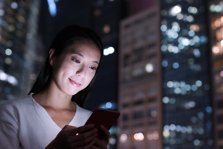 young Asian woman on mobile phone with modern city skyline behind